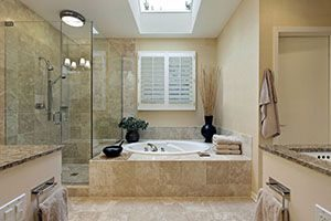 bathroom with natural stone tile floors and walls
